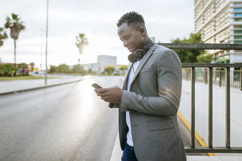 Young man standing at roadside looking at smartphone - KIJF01558