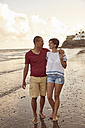Couple in love strolling face to face on the beach at sunset - PACF00008