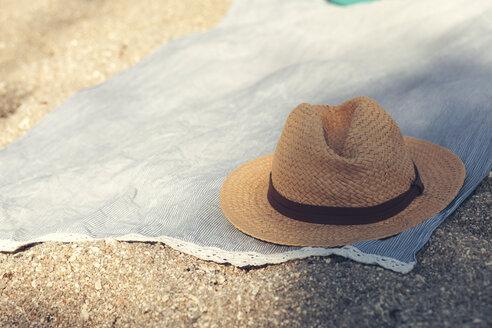 Straw hat on cloth on sandy beach - BZF00365