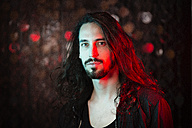 Portrait of bearded long-haired young man in red light - DMOF00009