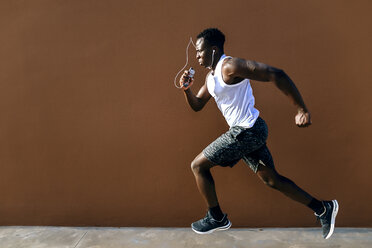 Young man running in front of brown wall - KIJF01579