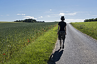 Germany, Bavaria, Leinach, man walking in rural landscape - NDF00654