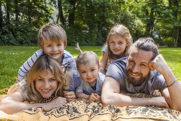 Portrait of happy family lying on meadow - TCF05435