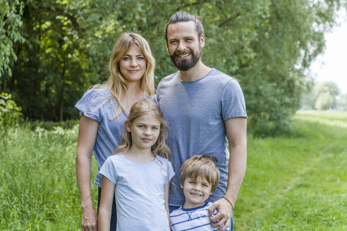 Portrait of happy family standing on meadow - TCF05444