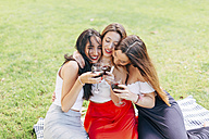 Happy friends in a park hugging and enjoying red wine - JPF00231