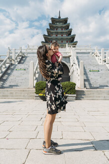 South Korea, Seoul, woman holding and kissing a baby girl in front of the National Folk Museum of Korea, inside Gyeongbokgung Palace - GEMF01690
