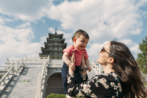 South Korea, Seoul, happy woman holding a baby girl in front of the National Folk Museum of Korea, inside Gyeongbokgung Palace - GEMF01693