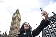 UK, London, happy woman taking selfie with smartphone in front of Big Ben - ABZF02102