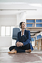 Smiling businesswoman sitting on the floor in a loft listening music with headphones - JOSF01163