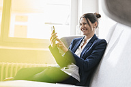 Laughing businesswoman sitting on a couch using her cell phone - JOSF01169