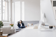 Businesswoman sitting on couch in a loft using cell phone - JOSF01172