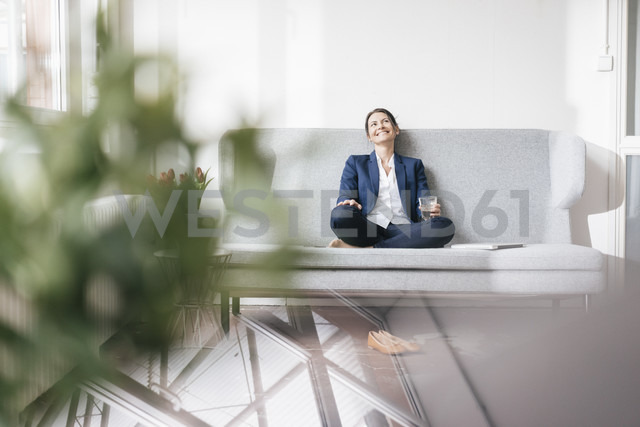 Smiling businesswoman sitting on couch with beverage - JOSF01175 - Joseffson/Westend61