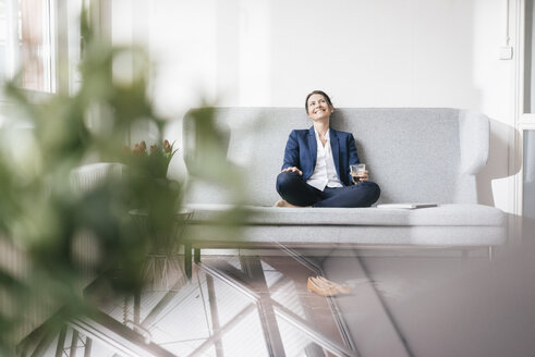 Smiling businesswoman sitting on couch with beverage - JOSF01175