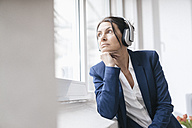 Portrait of woman looking out of the window while listening music with headphones - JOSF01178
