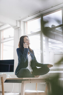 Businesswoman on the phone doing yoga exercise on desk in a loft - JOSF01184