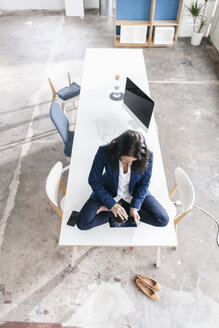 Businesswoman sitting on desk in a loft using tablet - JOSF01187