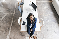 Smiling businesswoman sitting on desk in a loft - JOSF01190
