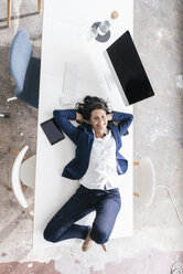Portrait of smiling businesswoman lying on desk in the office - JOSF01193