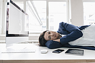 Businesswoman relaxing on desk in the office - JOSF01196