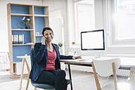 Portrait of businesswoman sitting at desk in a loft - JOSF01202