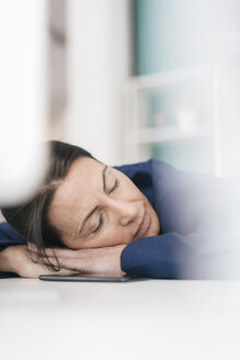 Overworked woman sleeping on laptop in office - JOSF01208