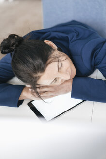Overworked woman sleeping on tablet in office - JOSF01211