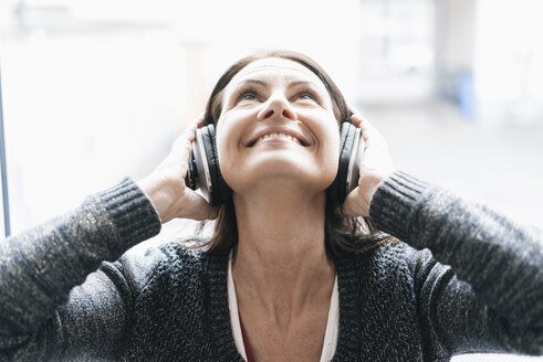 Portrait of smiling woman listening music with headphones looking up - JOSF01226