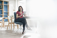 Portrait of smiling woman with tablet sitting at desk in a loft - JOSF01232