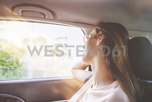 Woman traveling in car on the back seat - KIJF01586