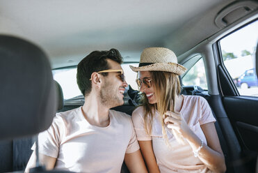 Couple laughing in the back seat of a car - KIJF01589