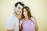 Smiling couple looking at camera in front yellow wall - KIJF01601