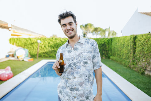 Young man drinking beer at the poolside - KIJF01613