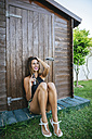 Young woman with beer sitting at wooden hut - KIJF01616