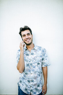 Man on cell phone in front of white wall - KIJF01625
