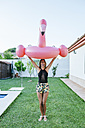 Woman holding pink flamingo float at the poolside - KIJF01628