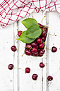 Cardboard box of cherries, leaves and kitchen towel on white wood - LVF06160