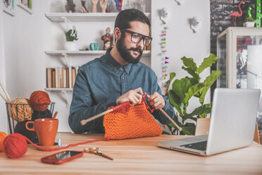Bearded man knitting at home using laptop for watching online tutorial - RTBF00902