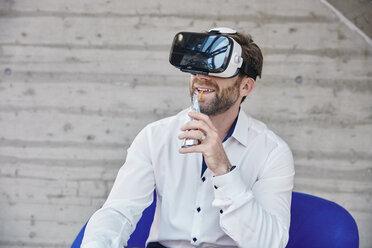 Man sitting on chair wearing VR glasses - RHF01943
