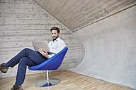 Businessman sitting on chair using laptop - RHF01946