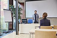Coach talking to woman in training room - RHF01949