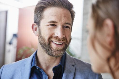 Smiling businessman looking at businesswoman - RHF01958