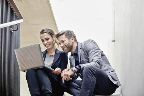 Businessman and businesswoman sitting on stairs in office sharing laptop - RHF01961