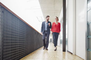 Businessman and businesswoman walking on office floor - RHF01973