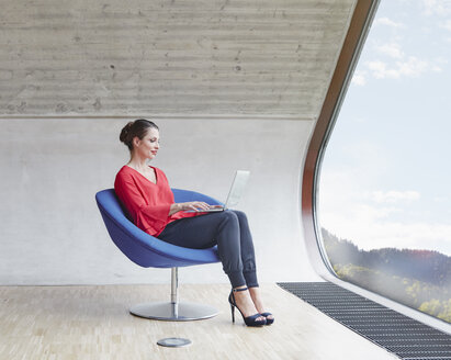 Woman sitting on chair in attic office using laptop - RHF01994