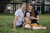 Happy parents sitting on a meadow with little son - MFF03652