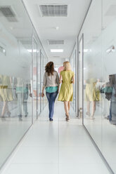 Two female colleagues walking in office corridor - ZEDF00645