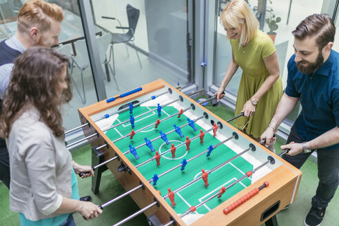 Colleagues playing foosball in office - ZEDF00648