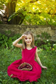 Portrait of little girl wearing red summer dress sitting on a meadow with basket of cherries - LVF06180