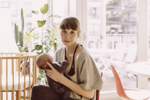Mother holding her newborn baby boy at home - MFF03665