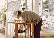Mother laying her newborn baby boy into crib - MFF03671